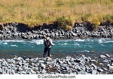 Fisherman fly fishing in Fiordland - FIORDLAND, NZ - JAN 15:...
