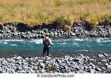 Fisherman fly fishing in Fiordland - FIORDLAND,NZ - JAN...
