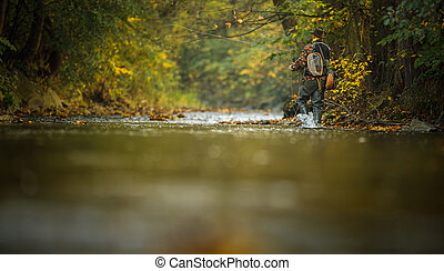 Fisherman  fly fishing on a splendid mountain river for rainbow trout