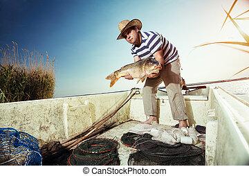 fisherman holding a big carp