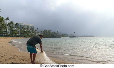 Fisherman holding fishing net in the beach 4k - Senior...