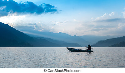 fisherman in a boat on the lake in Pokhara