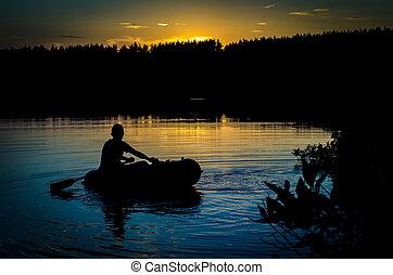 Fisherman in boat at sunset