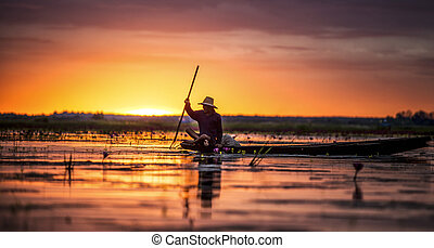 Fisherman in his traditional boat at sunrise