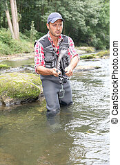 Fisherman in river with fishing rod