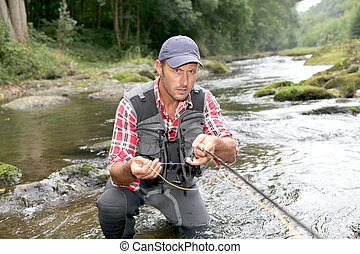 Fisherman in river with fly fishing rod