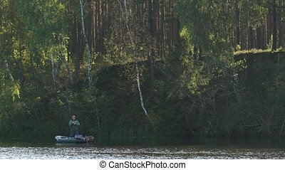 Fisherman in rubber boat throws a fishing pole with spoon-bait, jigs, spinner on river. Man stands and fishing on lake in sunny forest