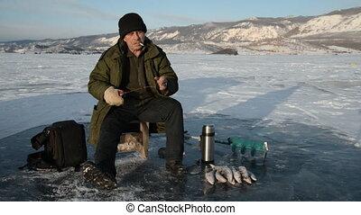 Fisherman is a man in winter fishing.