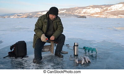 Fisherman is a man in winter fishing. A real fisherman is...