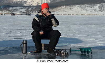 Fisherman is a man in winter fishing. - Modern hipster...