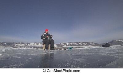 Fisherman is a man in winter fishing. - Fisherman's guy on...