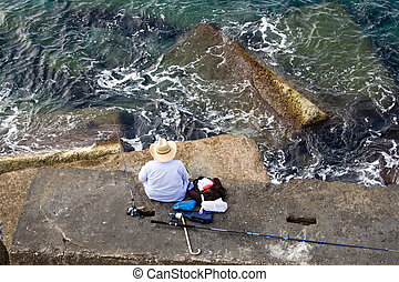 Fisherman is fishing on the sea stone, top horizontal view