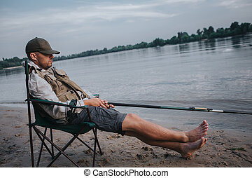 Fisherman is sitting in folding chair and sleeping. His cap is lying on eyes. Man holds fly rod in hands. He is fishing. It is evening outside.