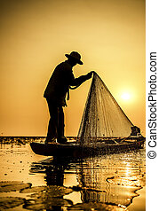 Fisherman of Lake in action when fishing, Thailand