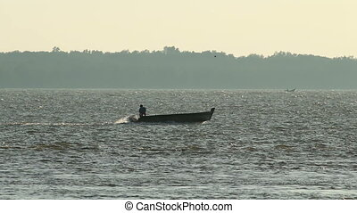Fisherman on a Boat - A lone fisherman on a speed boat