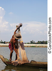 Fisherman on a wooden barge with net on the river