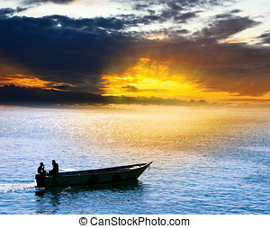 fisherman on boat at sunset