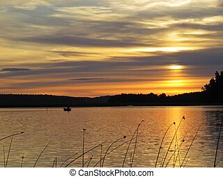 Fisherman on Boat Behind Reeds at Sunset Over Beautiful Lake with Cloudy Sky in background
