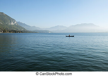 Fisherman on his boat on lake Annecy and foreground of...