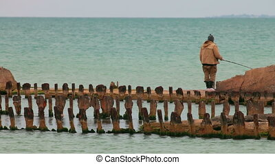 fisherman on old destroyed pier