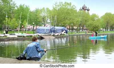 Fisherman on pond in city park, family sail on boat at background of church behind trees