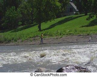 Fisherman on River Bank at Dam