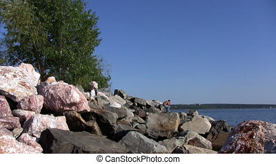 Fisherman on rocky shore