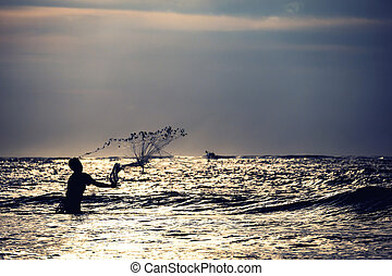 Fisherman on the beach at sunset in Bali