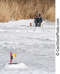 Fisherman on the lake ice fishing rod