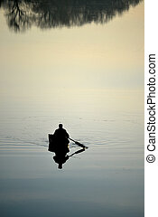 fisherman on the river with a mirror reflection of water