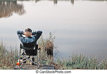 Fisherman on the shore of a large lake.