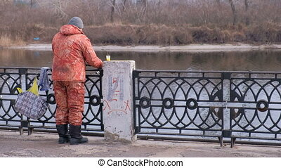 Fisherman on the waterfront - Fisherman in camouflage suit...