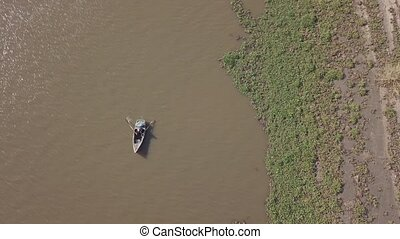 Aerial view of fisherman paddling with nests in his boat on Incomati River, Macaneta Beach, Maputo Province, Mozambique