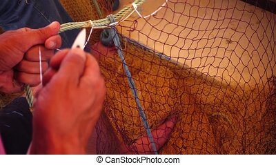 Fisherman Repairs Fishnet
