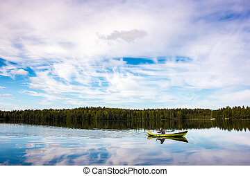 Fisherman sails on a green boat on the lake