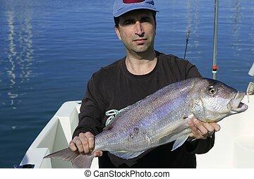 Fisherman showing proud catch saltwater fish
