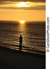 Fisherman silhouette at sunset.