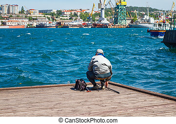 fisherman sitting on the pier fishing, relax