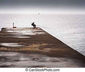 Fisherman sleeping on a pier on a foggy day at sea