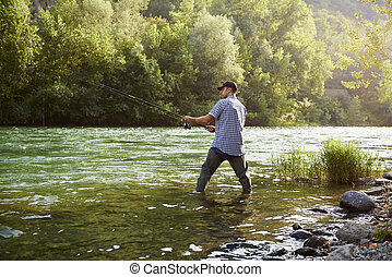 Fisherman standing near river and holding fishing rod - mid...