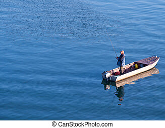 Fisherman standing on a boat and fishing in sea