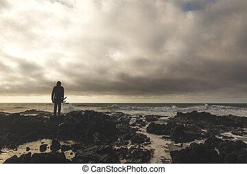 Fisherman Standing on Rocky Shore