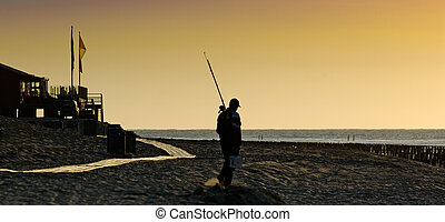 Fisherman in the dawn at the beach of the northsea in the...