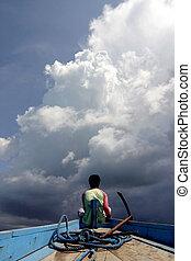 Fisherman - Indonesian fisherman watching big clouds coming...