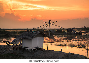fisherman village with giant fish net at sunset