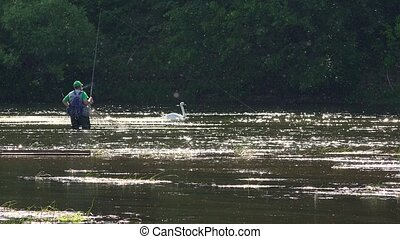 fisherman wade though deep wild water river and active people with canoes.