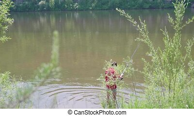 Fisherman with a fishing rod is on the river Bank. Beautiful summer landscape. Outdoor recreation. Hobby