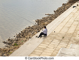 Fisherman with a fishing rod on the city embankment of the river
