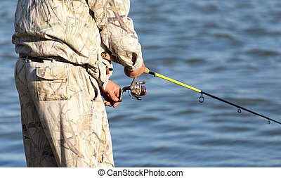 fisherman with a fishing rod on the river