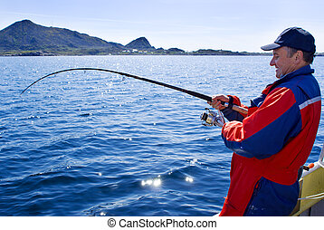 Fisherman with a spinning - Fisherman with fish on the boat...